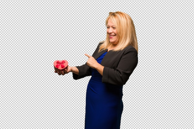 Middle aged latin woman celebrating valentines day pointing to the side with finger