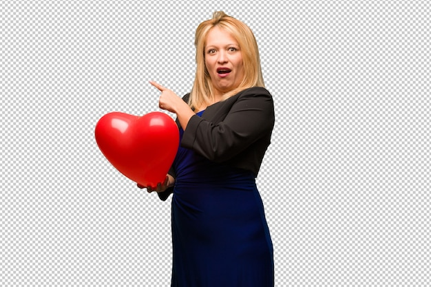 Middle aged latin woman celebrating valentines day pointing to the side