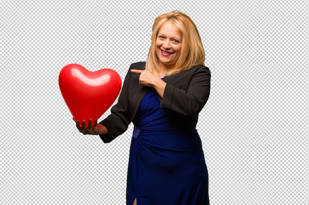 Middle aged latin woman celebrating valentines day smiling and pointing to the side