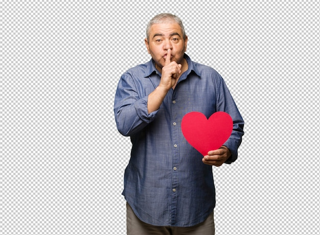 Middle aged man celebrating valentines day keeping a secret or asking for silence