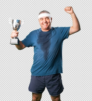 Middle aged man doing winner gesture holding a trophy