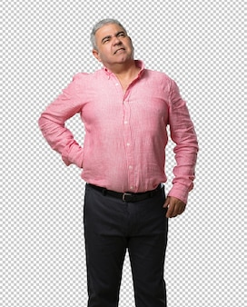 Middle aged man with back pain due to work stress, tired and astute