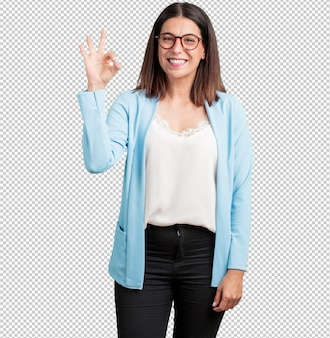 Middle aged woman cheerful and confident making ok gesture
