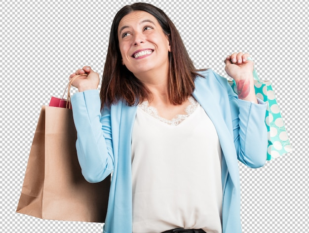 Middle aged woman cheerful and smiling, very excited carrying a shopping bags