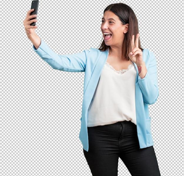 Женщина средних лет уверенная и жизнерадостная, делающая селфи, с забавным и беззаботным жестом смотрящая на мобильный телефон, серфинг в социальных сетях и интернете
