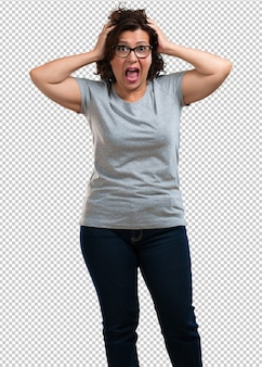Middle aged woman frustrated and desperate, angry and sad with hands on head