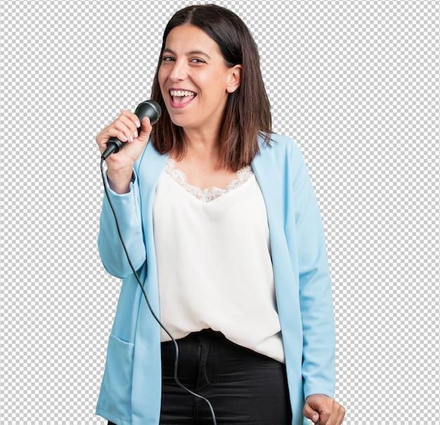 Женщина средних лет счастлива и мотивирована, поет песню с микрофоном, представляет событие или устраивает вечеринку, наслаждается моментом