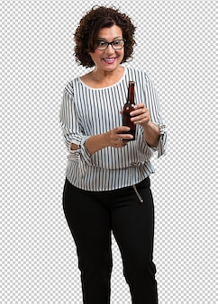 Middle aged woman happy and fun, holding a bottle of beer, feels good after an intense day of work, ready to watch a soccer match on television