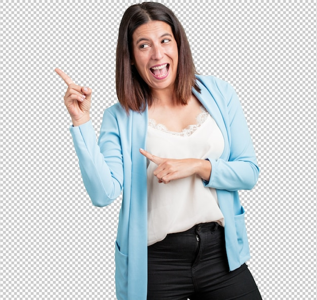 Middle aged woman pointing to the side, smiling surprised presenting something, natural and casual