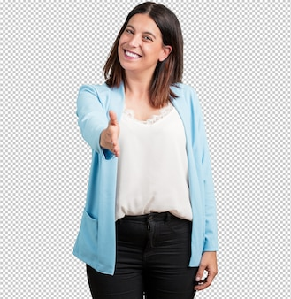 Middle aged woman reaching out to greet someone or gesturing to help, happy and excited
