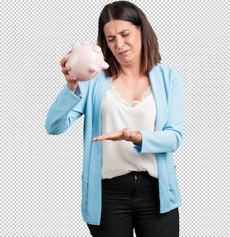 Middle aged woman sad and disappointed, holding a piglet bank, no money left, trying to get something out, face of anger and anguish, concept of poverty