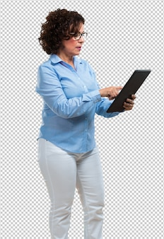 Middle aged woman smiling and confident, holding a tablet, using it to surf the internet