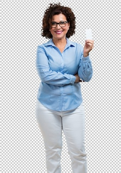 Middle aged woman smiling confident, offering a business card, has a thriving business, copy space to write whatever you want