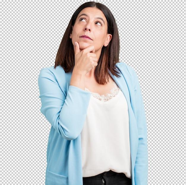 中年の女性が考えて見上げると、アイデアについて混乱して、解決策を見つけようとしている