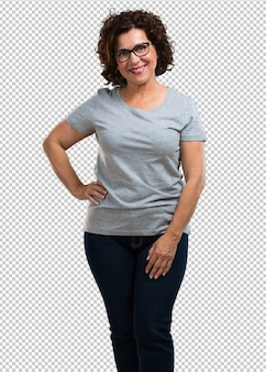 Middle aged woman with hands on hips, standing, relaxed and smiling, very positive and cheerful