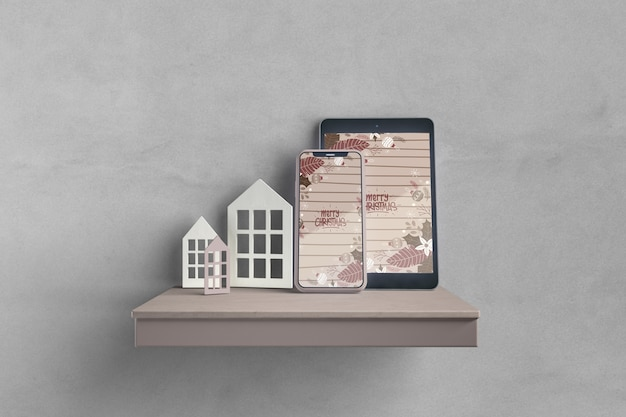 Miniatures of house on shelf beside electronic devices