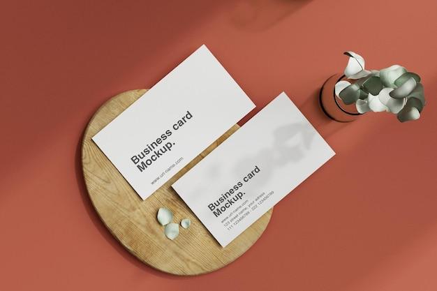 Минимальный макет визитной карточки на фоне деревянной небольшой пластины