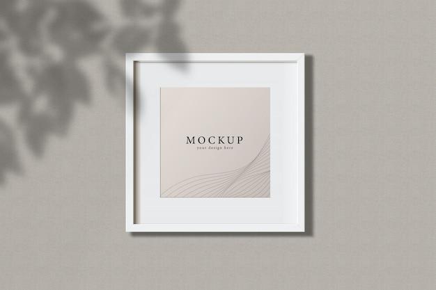 Минимальная пустая квадратная белая рамка изображение макет висит на фоне стены с листьями окна. изолировать векторные иллюстрации.