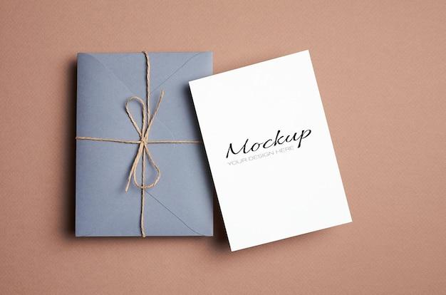 베이지 색 종이 배경에 봉투와 최소한의 스타일 고정 카드 모형