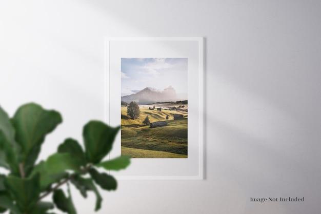 ミニマリストでリアルな白いフレームのモックアップまたはリアルな葉と影の壁のムードボード