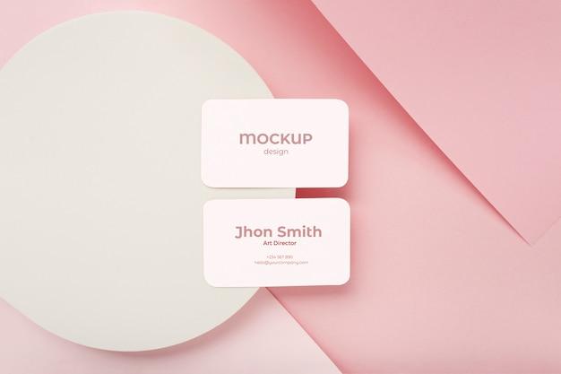 분홍색과 흰색 색상으로 기하학적 배경에 미니멀리스트 명함 모형 구성