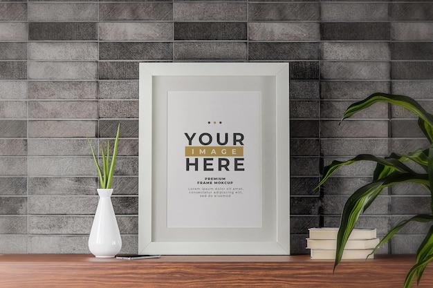 ミニマリストの白いフォトフレームモックアップポスター黒レンガの壁