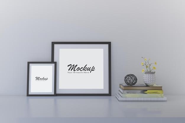 책이 있는 흰색 선반에 2개의 사진 프레임 모형이 있는 인테리어의 미니멀한 가정 장식