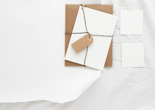 ベッドの上のギフト包装と文房具カードのミニマルな水平モックアップ