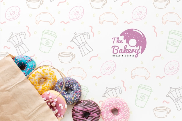 Mix of colorful donuts in paper bag with mock-up