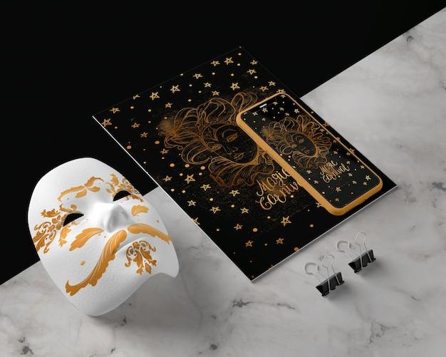 Мобильный рядом с золотой маской на столе