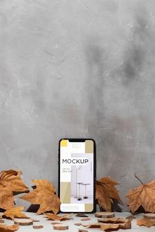 나뭇잎으로 둘러싸인 벽에 기대어 휴대 전화 모형