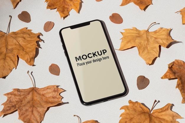 Макет мобильного телефона на столе в окружении листьев