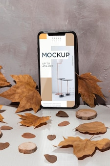 Mobile phone mockup standing on the table surrounded by leaves