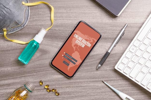 フェイスマスク、アルコールスプレー、オフィスの机の上のキーボードを備えた携帯電話のモックアップ