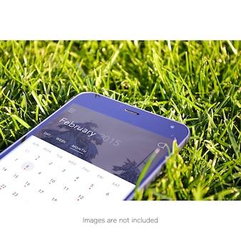Мобильный телефон на траве макет вверх