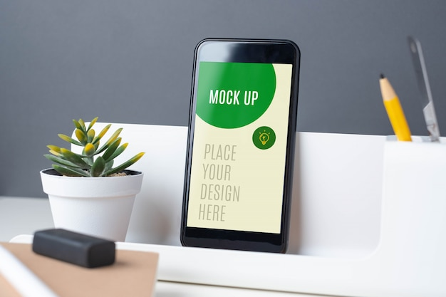 Мобильный телефон на пенале на офисном столе макете