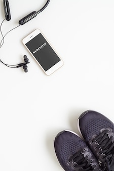 Mobilephone with bluetooth earphone and running shoes on white background