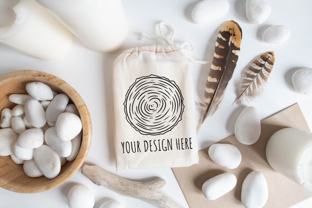 Mock up of cotton bag or pouch and bowl with white pebble and boho elements on white table.