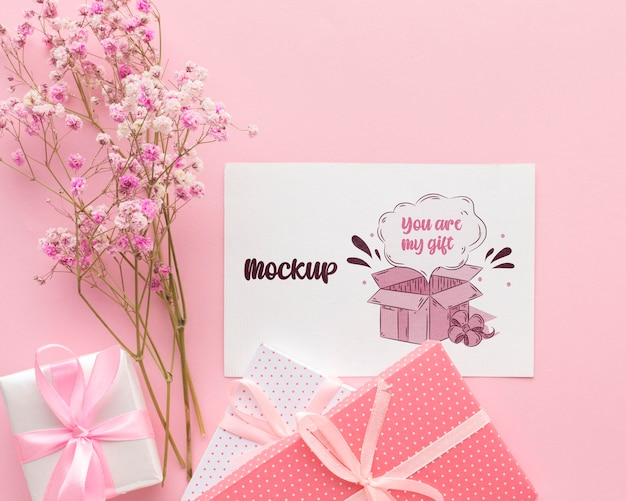 Mock-up cute card with wrapped gift and flowers