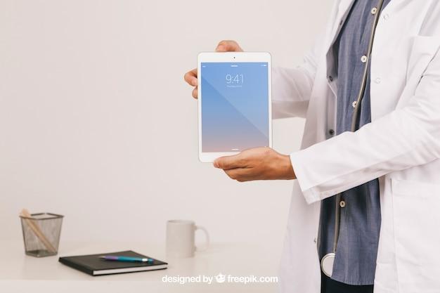 医者の手でタブレットを持たせたデザインをモックアップ