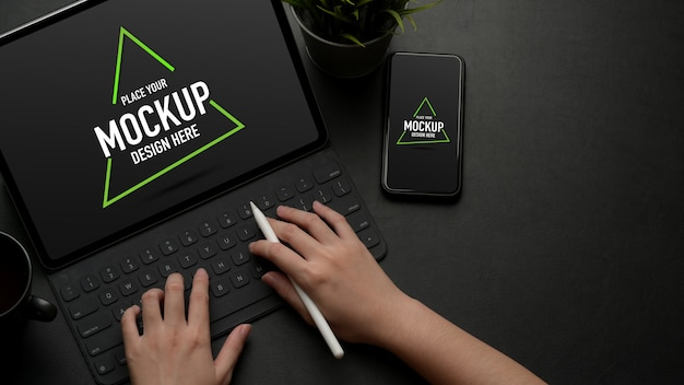Mock up digital tablet on black table with mock up smartphone and copy space Premium Psd