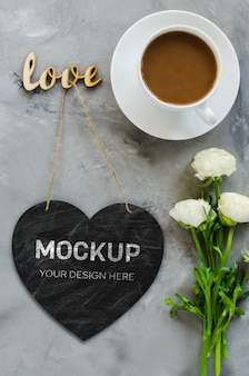Mock up of greeting card. empty chalk board heart shaped with coffee cup and flowers.