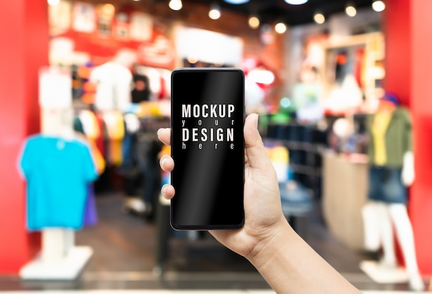 Mock up hand holding  phone in clothing store.