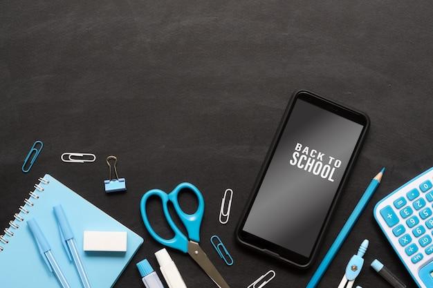 Макет мобильного телефона для обратно в школу фон концепции. школьные предметы на гранж черной доске текстуры фона с макетом смартфона