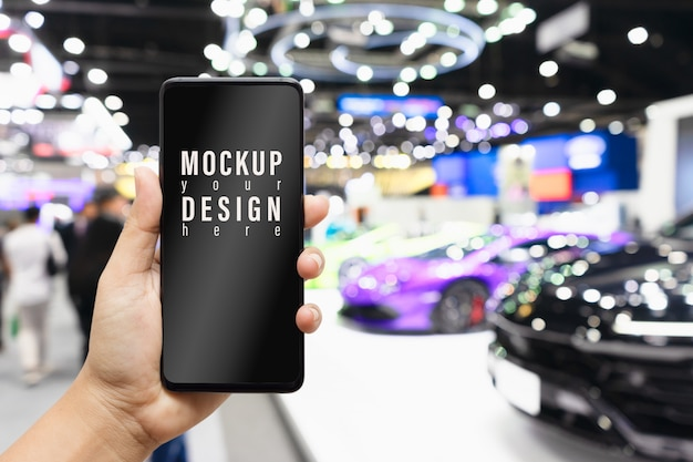 Mock up mobile phone with  blurred image of public event exhibition hall