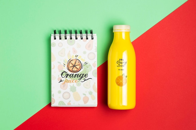 Mock-up notepad and plastic bottle with smoothie