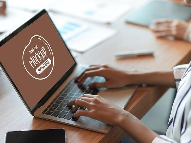 オフィスデスクのラップトップキーボードで入力する女性のモックアップ