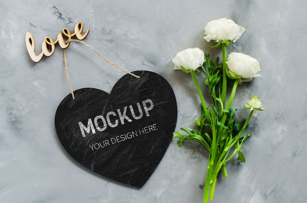 グリーティングカードのモックアップ。空のチョークボードハート形の花と碑文の愛。