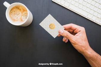 Mock up of hand holding business card with coffe and keyboard