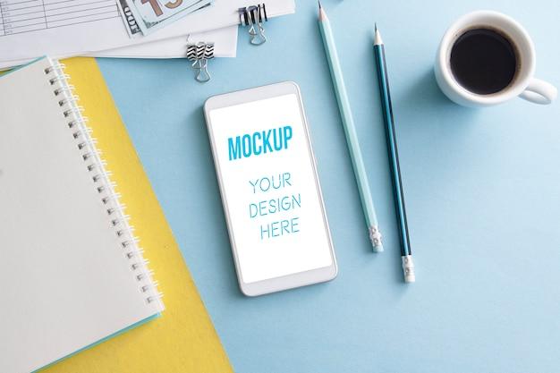 Макет смартфона на цветном рабочем столе с блокнотом, карандашами и чашкой кофе